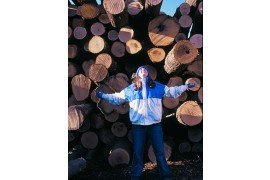 Girl stands in front of huge pile of cut logs
