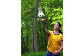 Girl in forest throws paper airplane