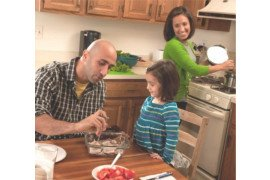 A father and daughter using a food thermometer while mom cooks in the background / SNAP-Ed Connection