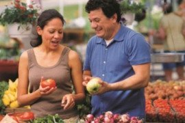 A man and woman look at produce at a farmers' market/SNAP-Ed Connection